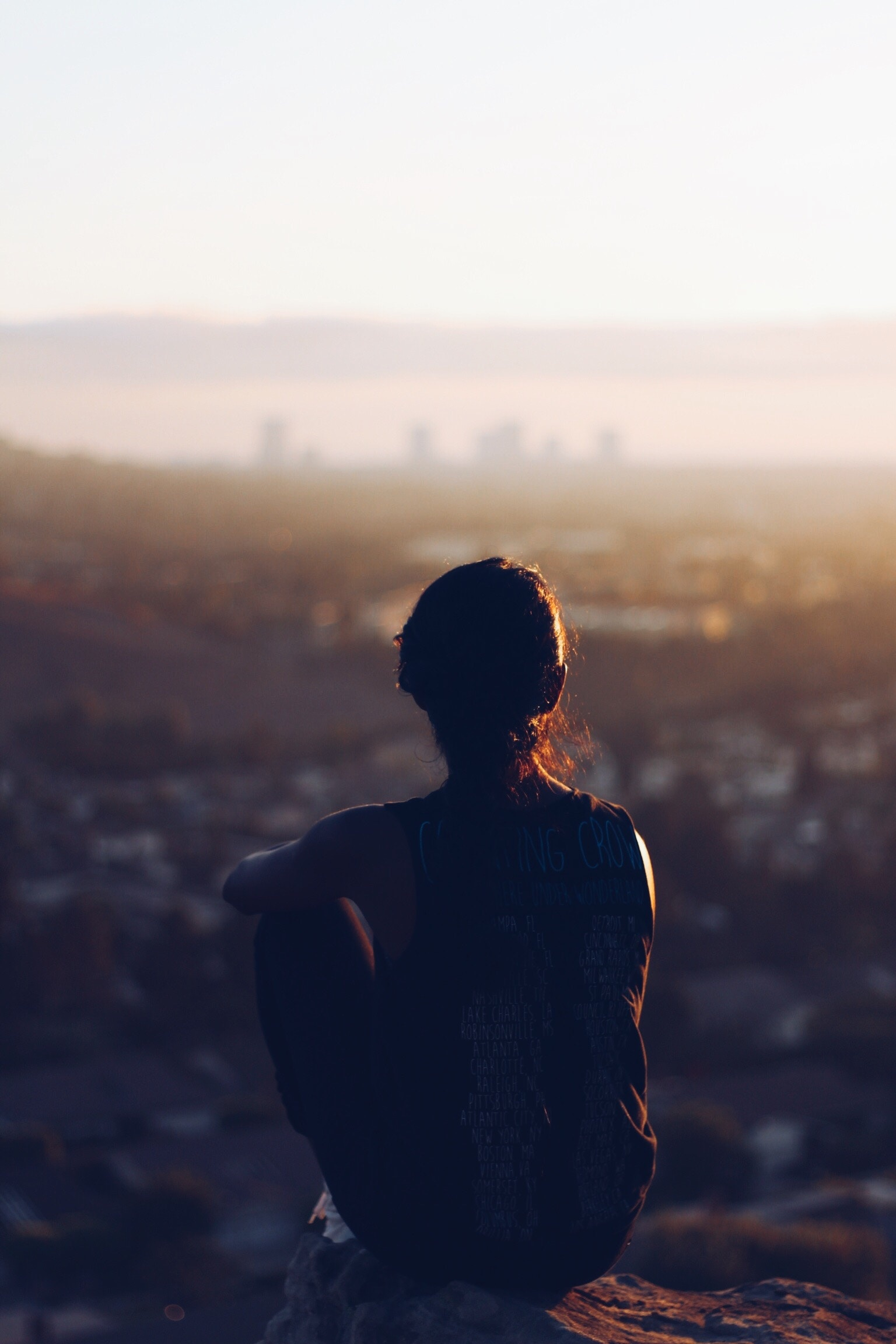Woman sitting on a high hill overlooking a city, getting some rest